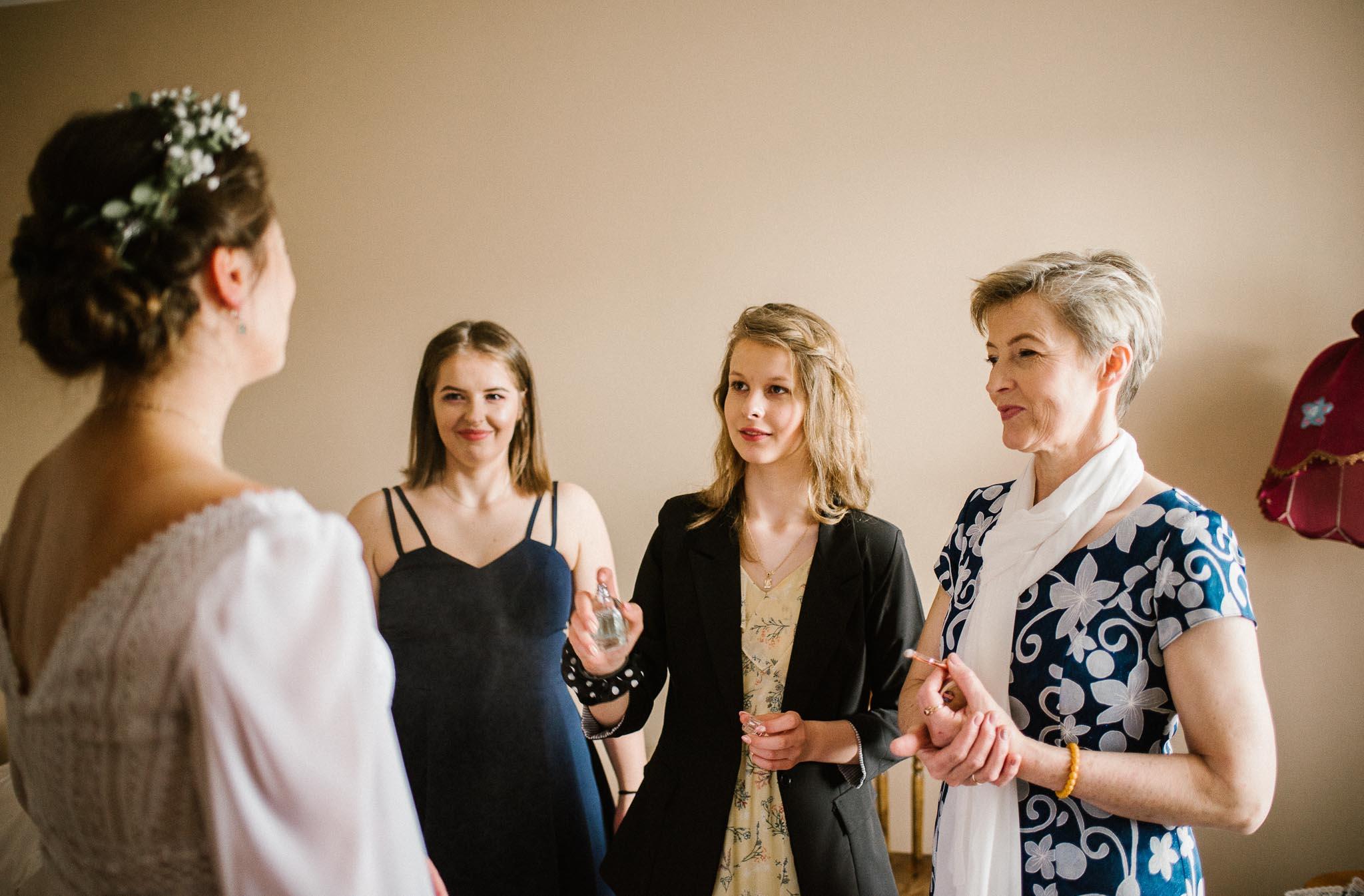 Kobiety oglądają pannę młodą w sukni ślubnej - sesja ślubna reportaż Żuczki Inowrocław