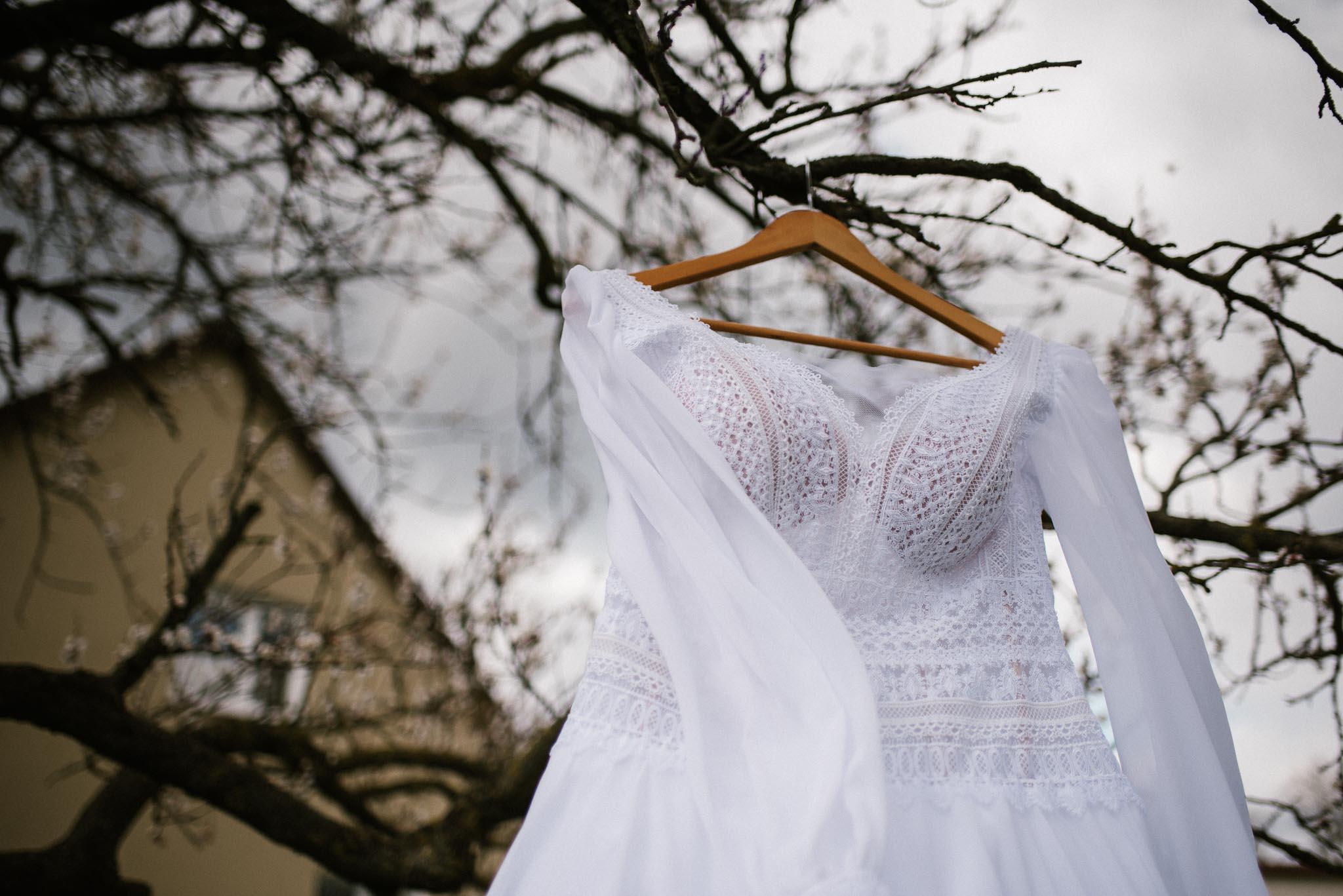 Suknia ślubna wisi na drzewie i powiewa na wietrze - sesja ślubna reportaż Żuczki Inowrocław