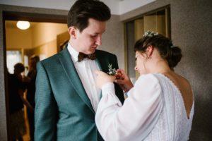 Panna młoda przypina panu młodemu kwiatek do butonierki - sesja ślubna reportaż Żuczki Inowrocław
