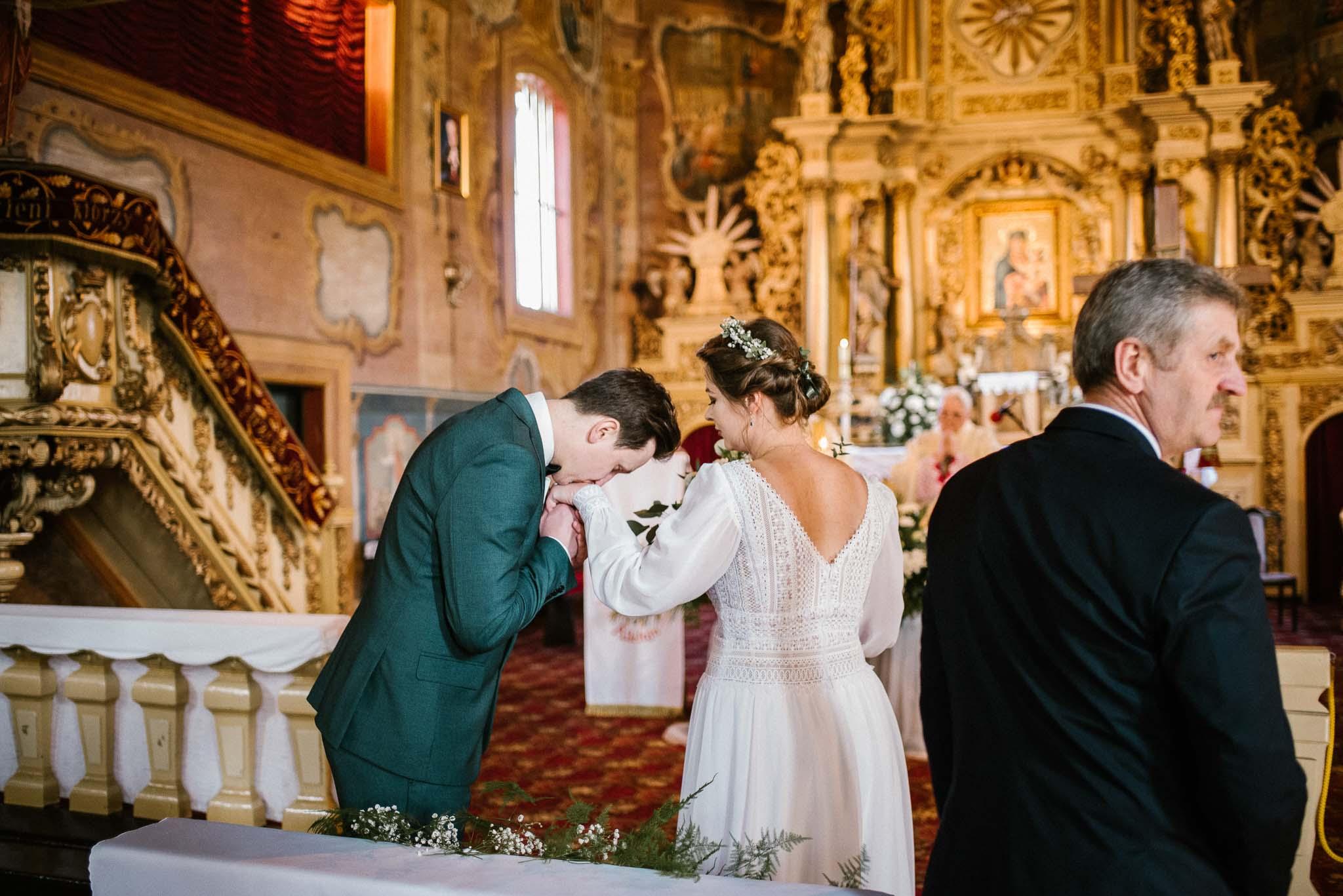 Pan młody całuje pannę młodą w rękę - sesja ślubna reportaż Żuczki Inowrocław