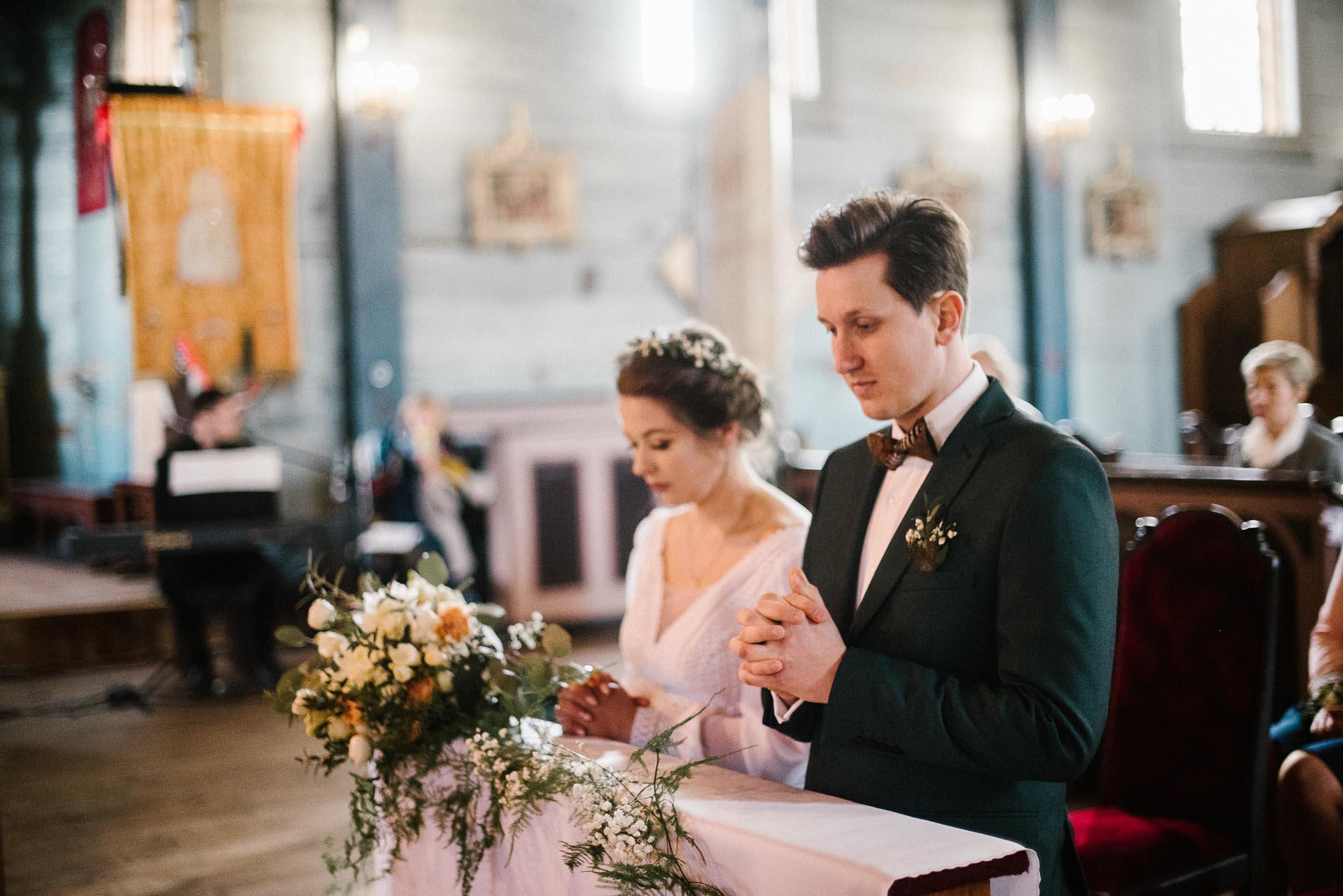 Para młoda klęczy przed ołtarzem - sesja ślubna reportaż Żuczki Inowrocław