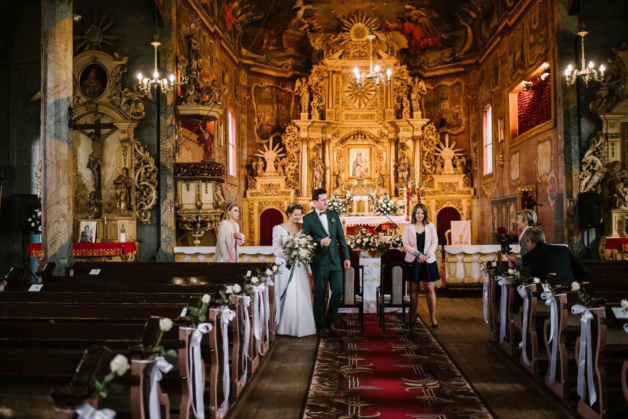 Para młoda wychodzi z kościoła  - sesja ślubna reportaż Żuczki Inowrocław