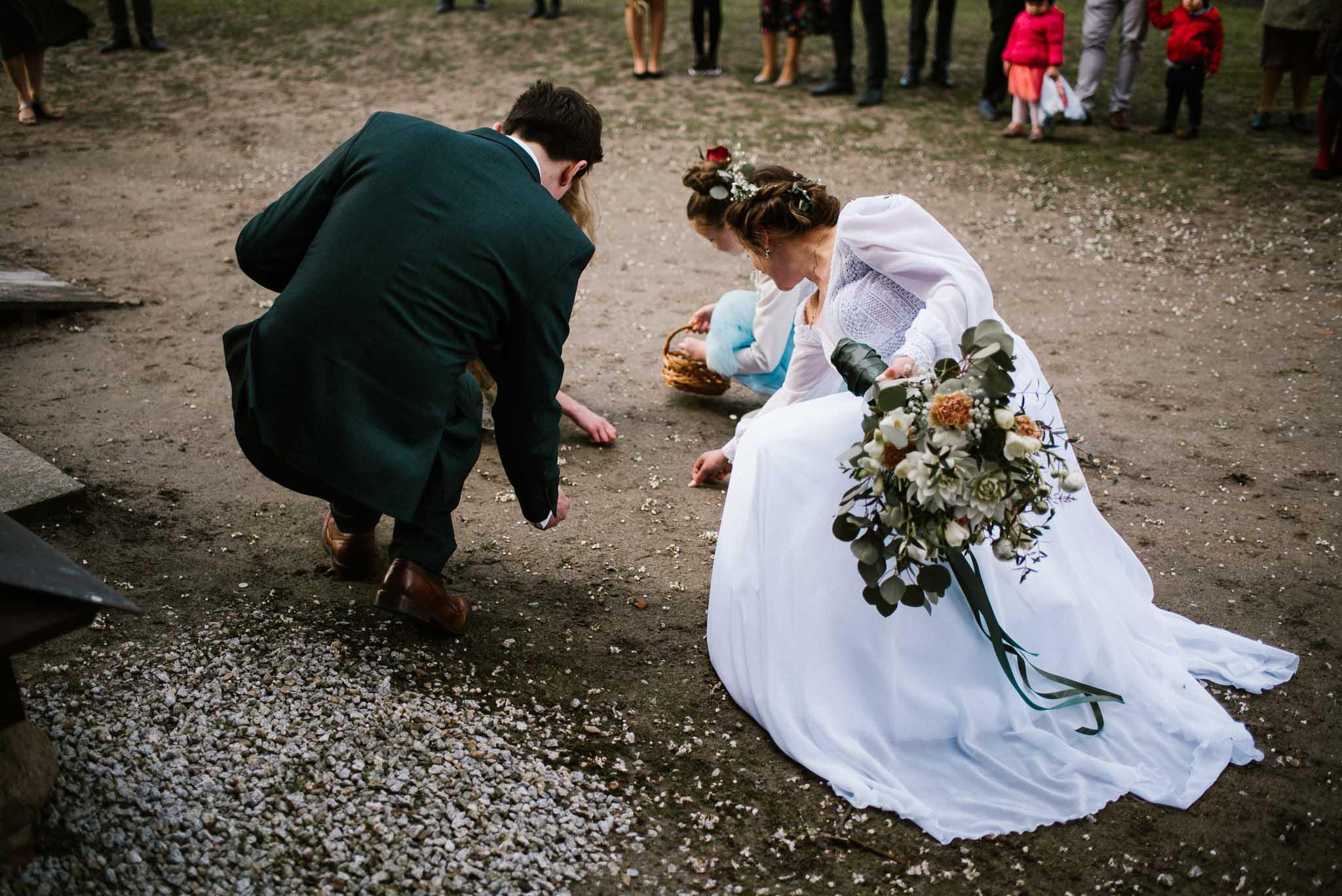 Para młoda zbiera monety przed kościołem - sesja ślubna reportaż Żuczki Inowrocław