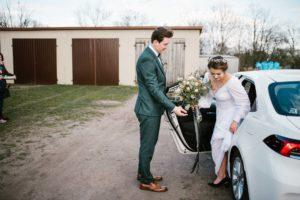 Pan młody pomaga żonie wysiąść z samochodu - sesja ślubna reportaż Żuczki Inowrocław