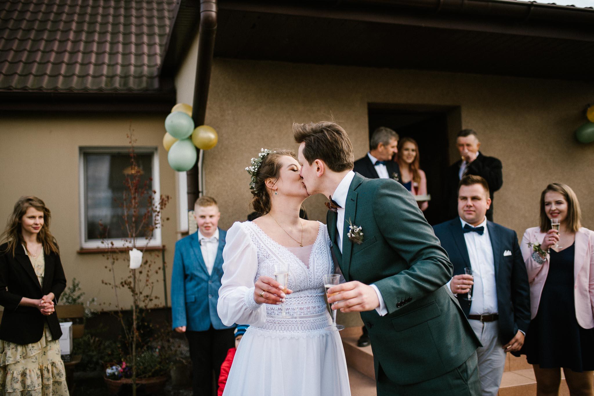 Para młoda całuje się przed domem i pija szampana - sesja ślubna reportaż Żuczki Inowrocław