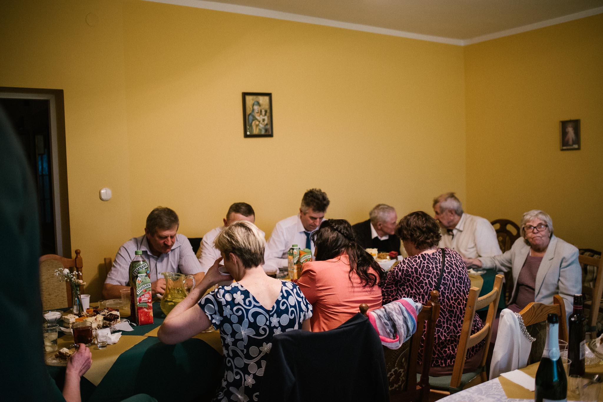 Goście siedzą w salonie na przyjęciu weselnym w domu - sesja ślubna reportaż Żuczki Inowrocław