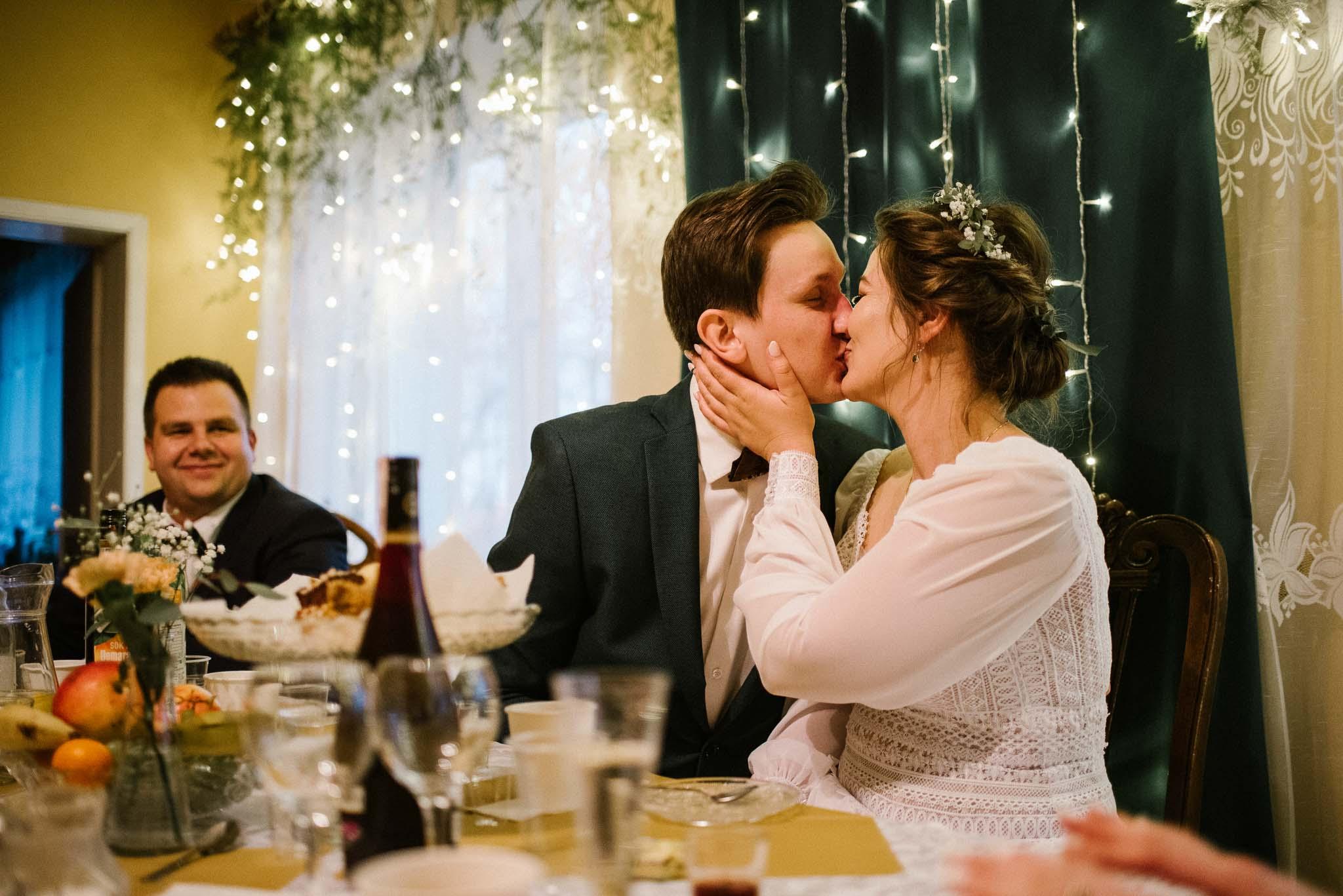 Para młoda przy stole się całuje - sesja ślubna reportaż Żuczki Inowrocław