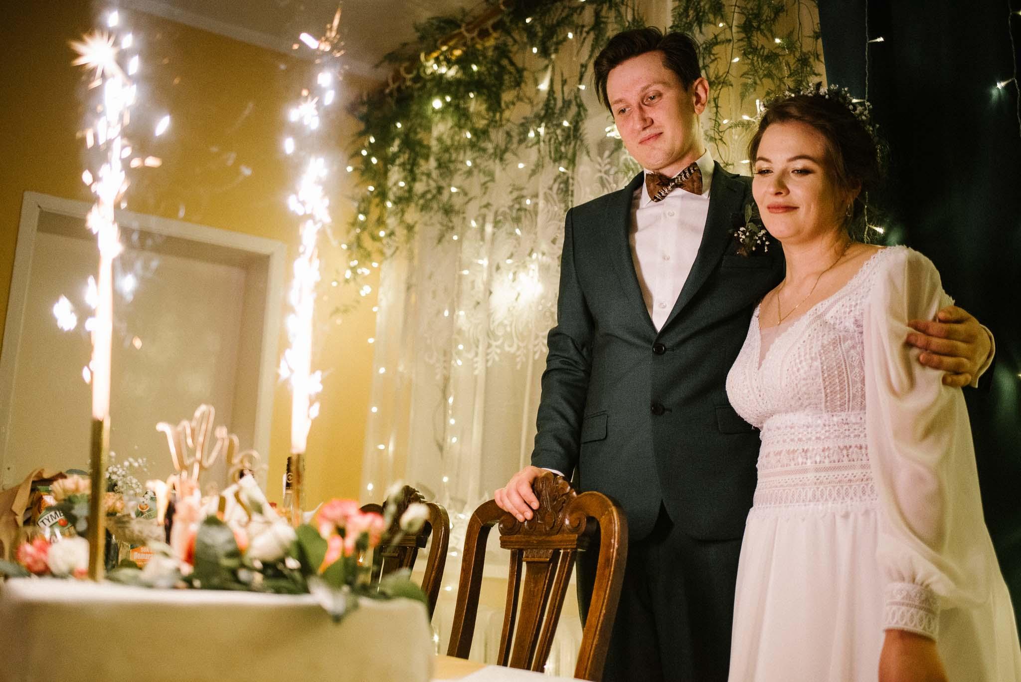 Para młoda patrzy na tort weselny -sesja ślubna reportaż Żuczki Inowrocław