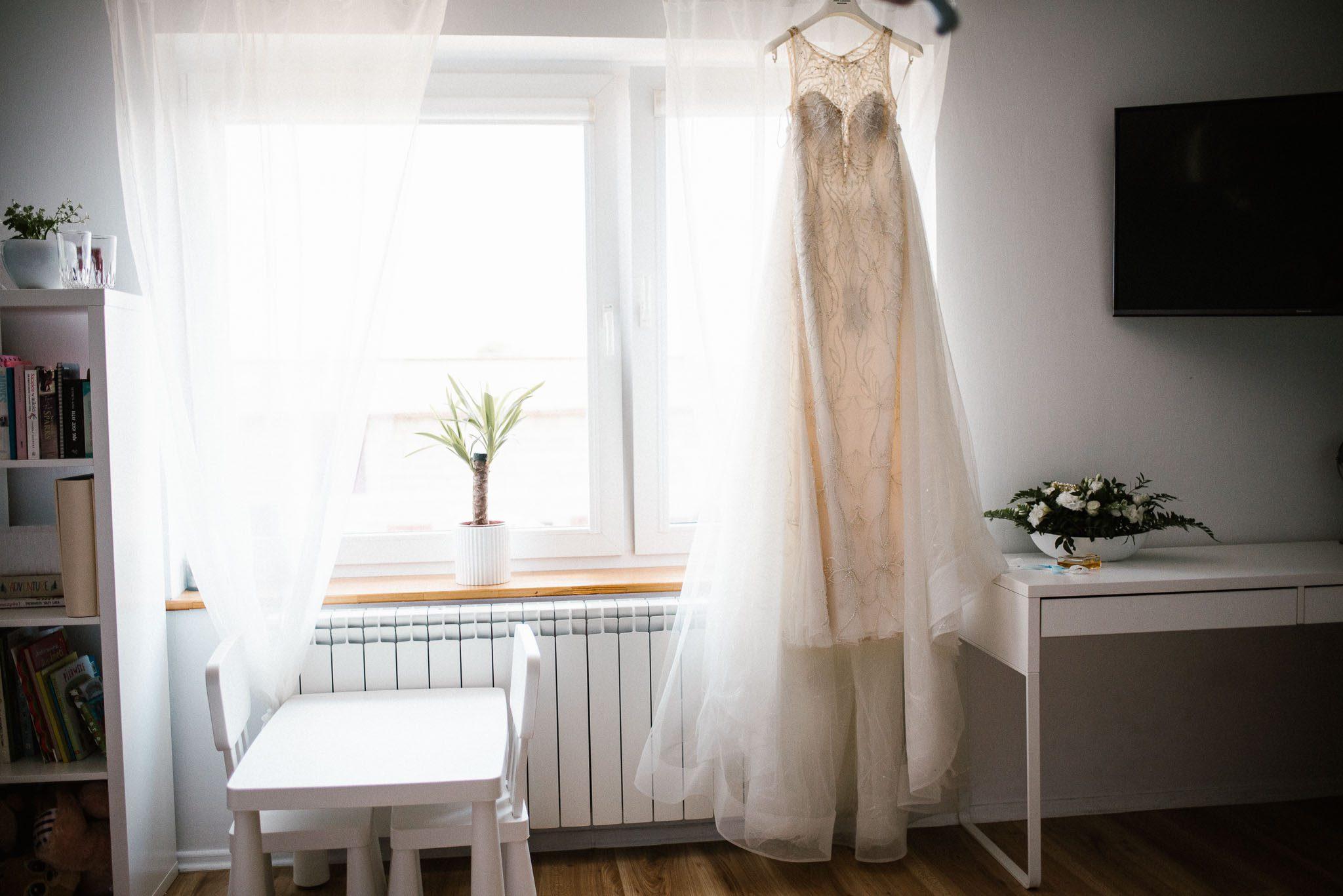 Suknia ślubna wisi przy oknie - ślub w Stodole Bojanowo