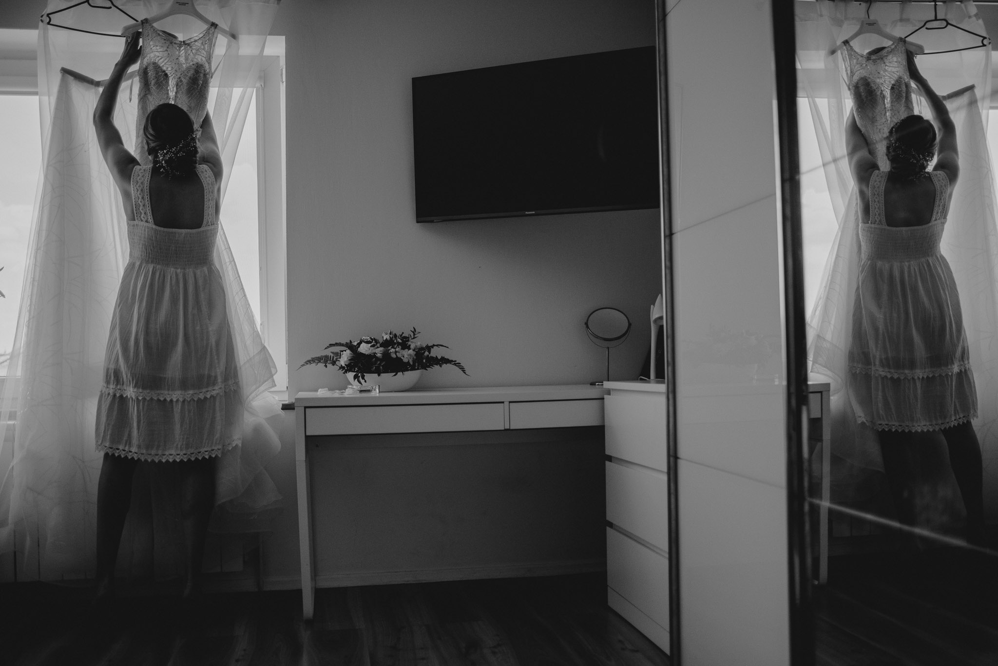 Panna młoda sięga suknię ślubną z wieszaka - ślub w Stodole Bojanowo