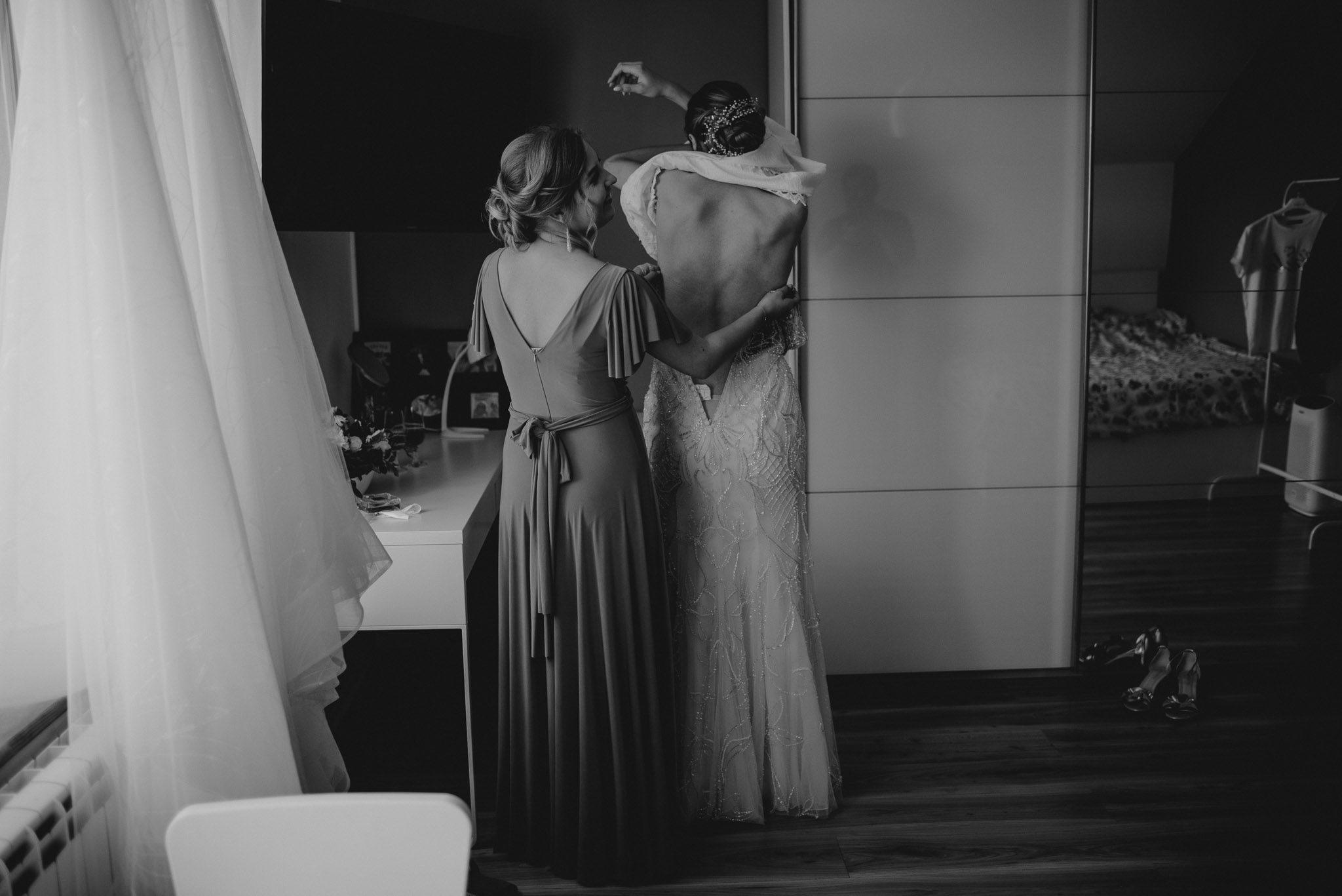 Świadkowa pomaga pannie młodej założyć suknię ślubną - ślub w Stodole Bojanowo