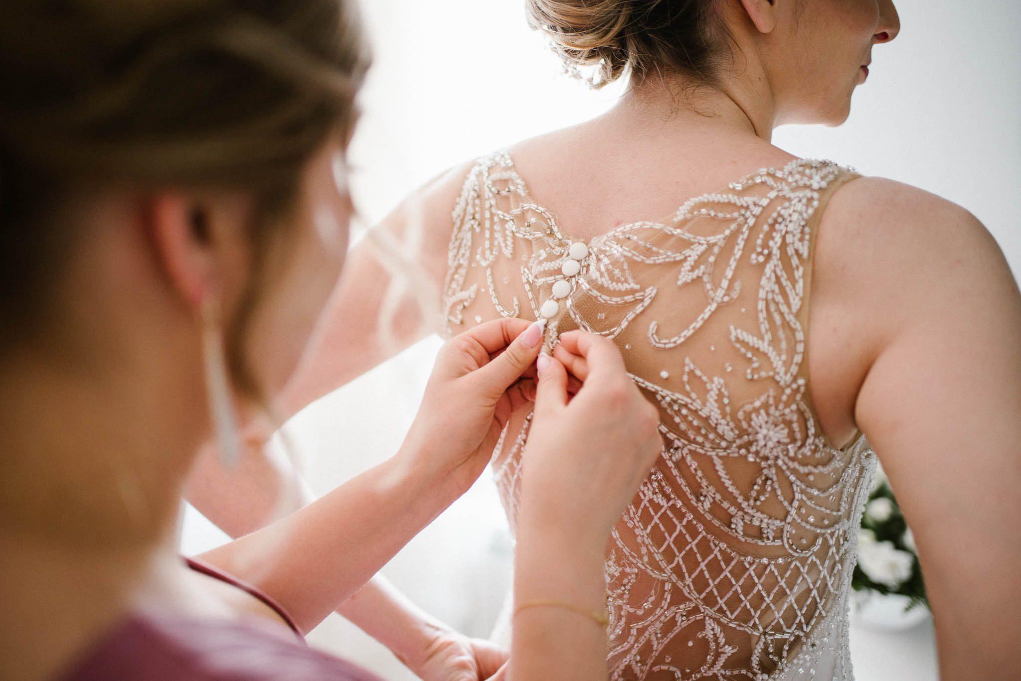 Świadkowa zapina guziki na sukni panny młodej - ślub w Stodole Bojanowo