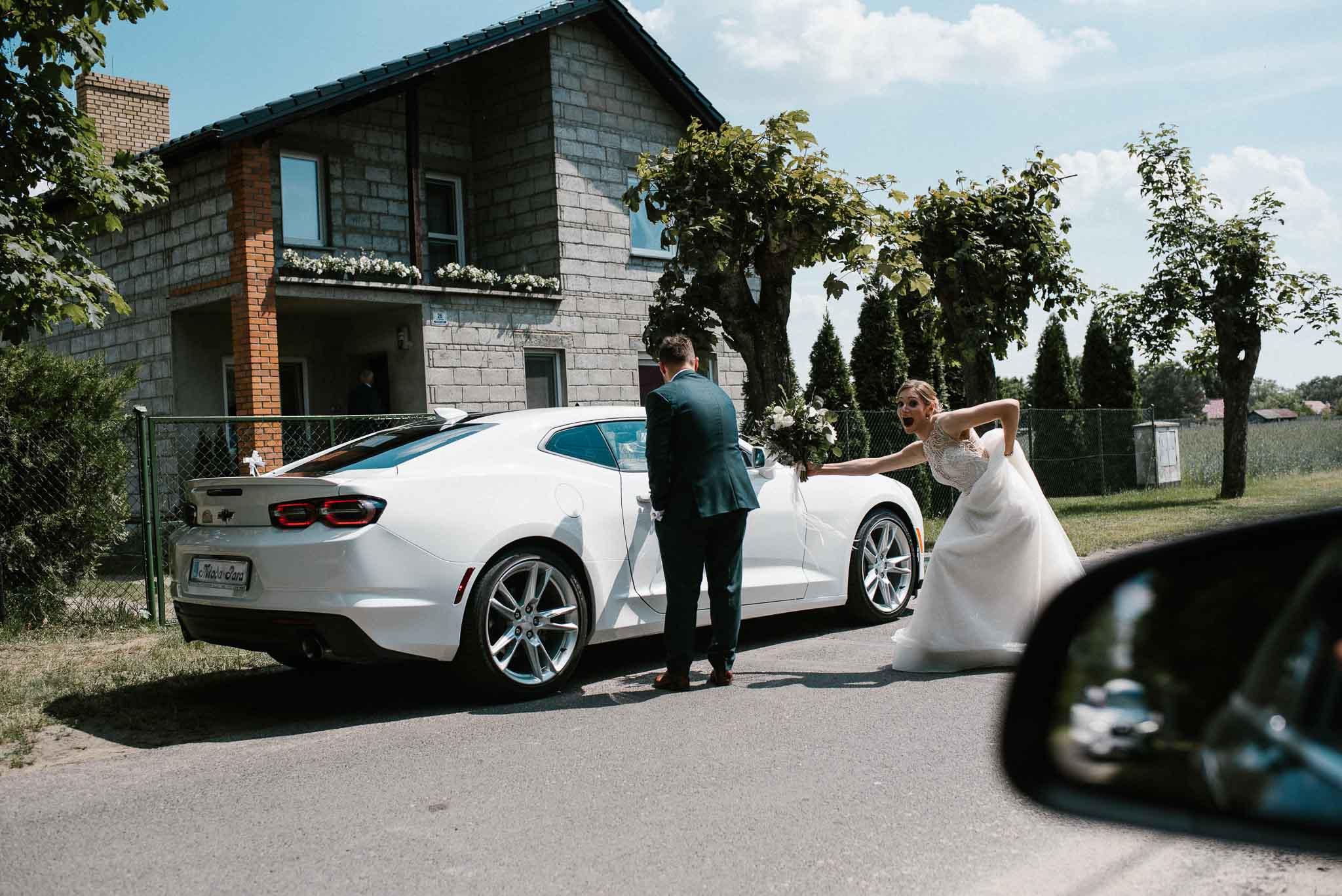 Para młoda wysiada z samochodu i idzie do kościoła - ślub w Stodole Bojanowo