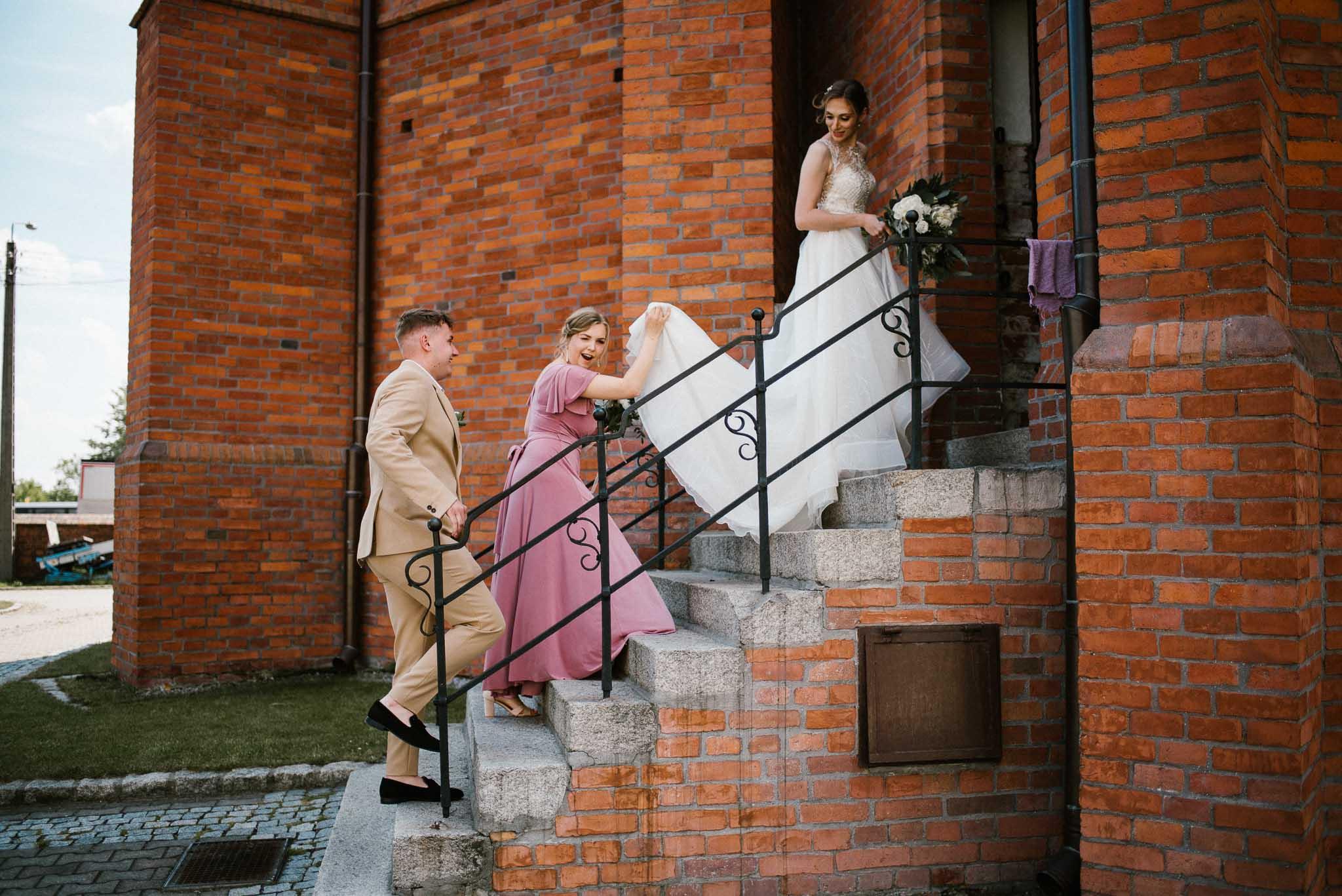 Para młoda ze świadkami wchodzą do kościoła - ślub w Stodole Bojanowo