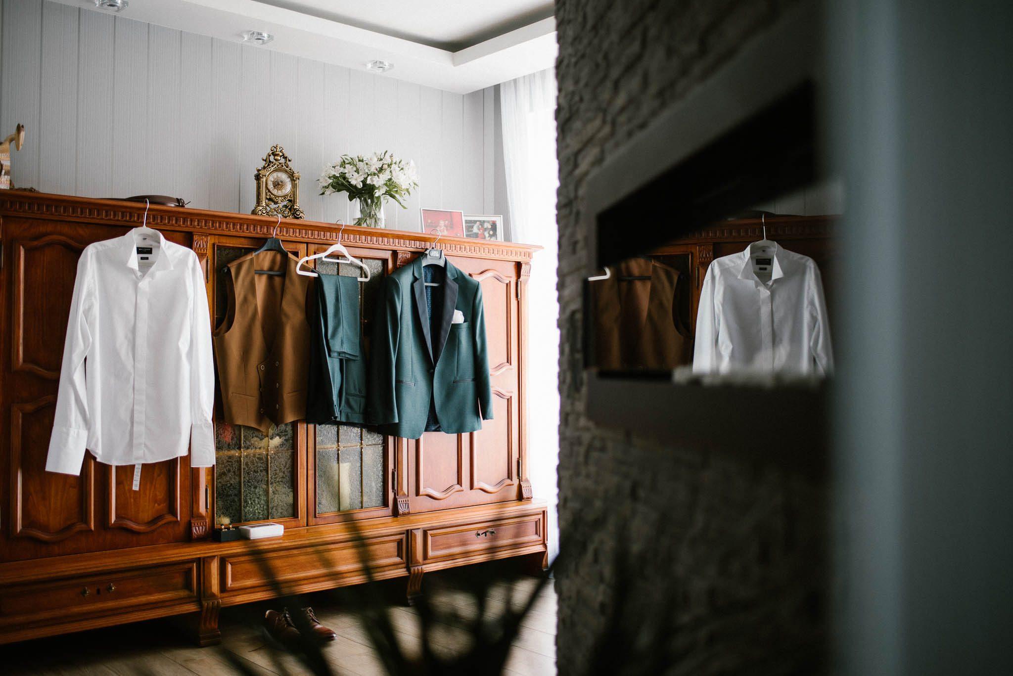 Garnitur ślubny pana młodego wisi na szafie - ślub w Stodole Bojanowo