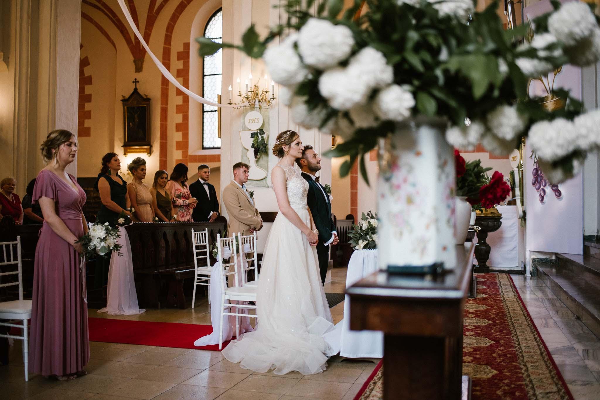 Para młoda stoi przed ołtarzem -  ślub w Stodole Bojanowo