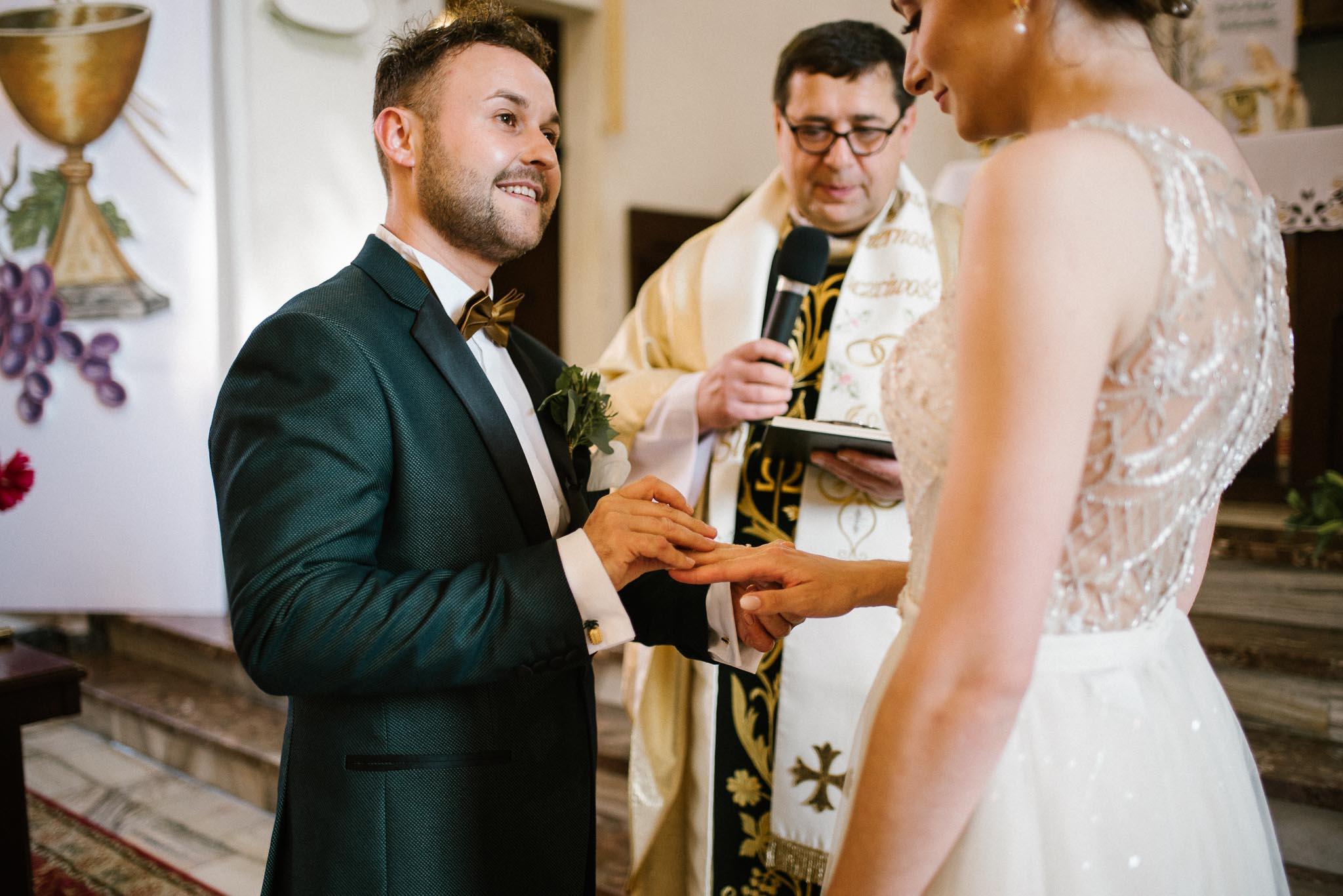 Pan młody zakłada żonie obrączkę -  ślub w Stodole Bojanowo