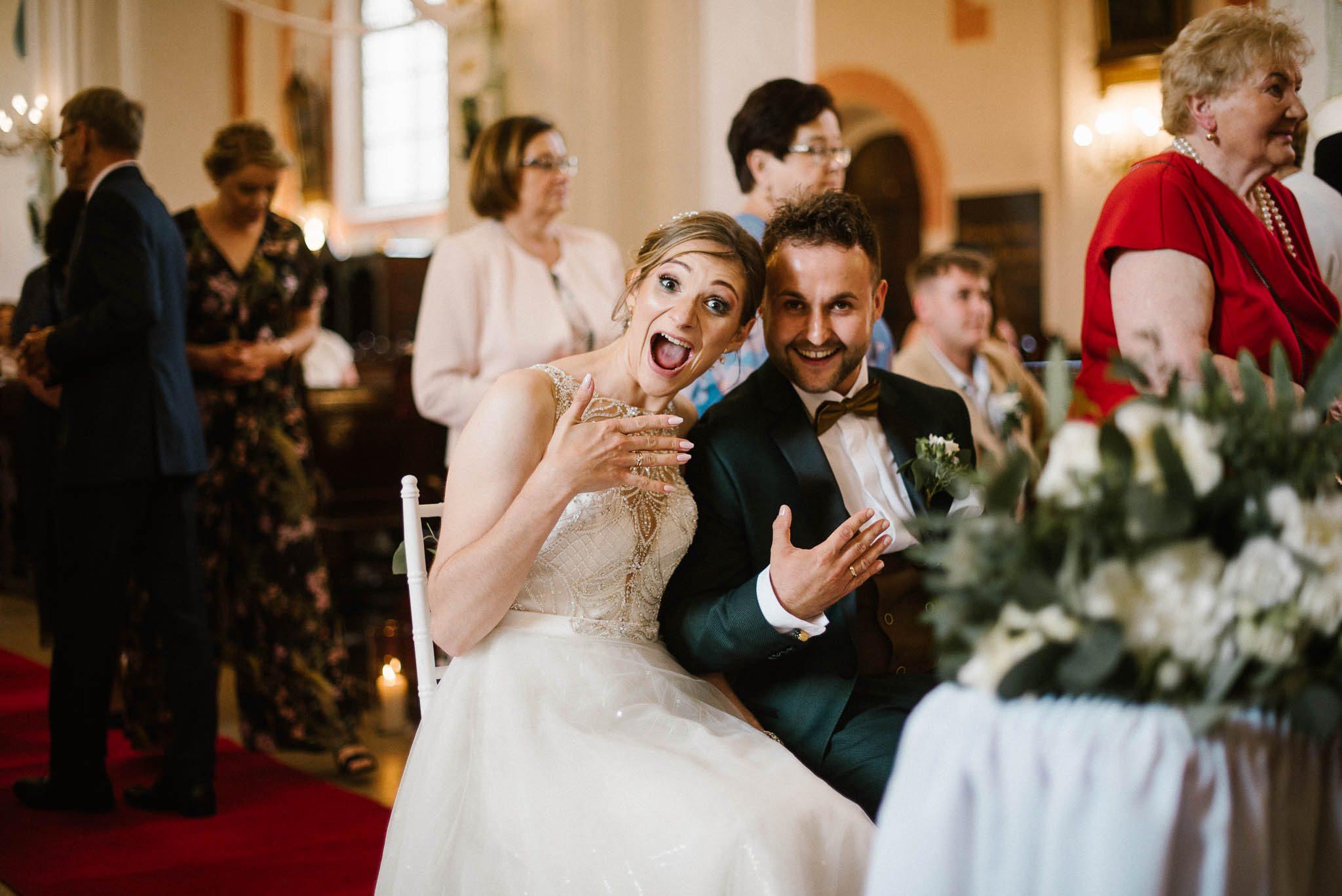 Para młoda pokazuje fotografce obrączki -  ślub w Stodole Bojanowo
