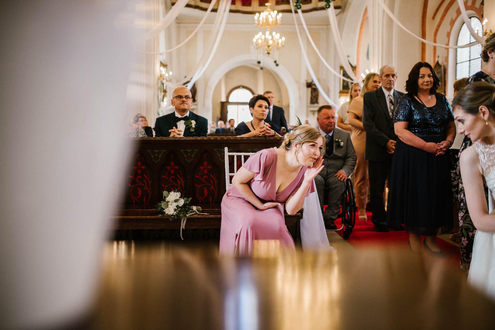 Świadkowa szepcze do pani młodej w kościele -  ślub w Stodole Bojanowo