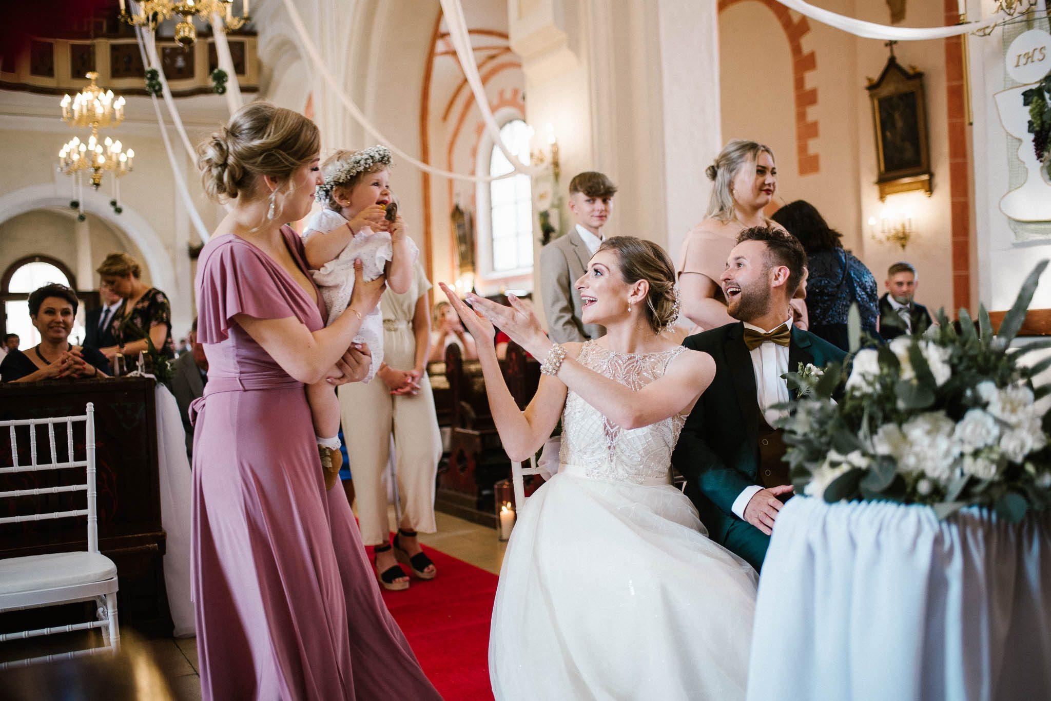 Świadkowa przynosi córeczkę rodzicom -  ślub w Stodole Bojanowo
