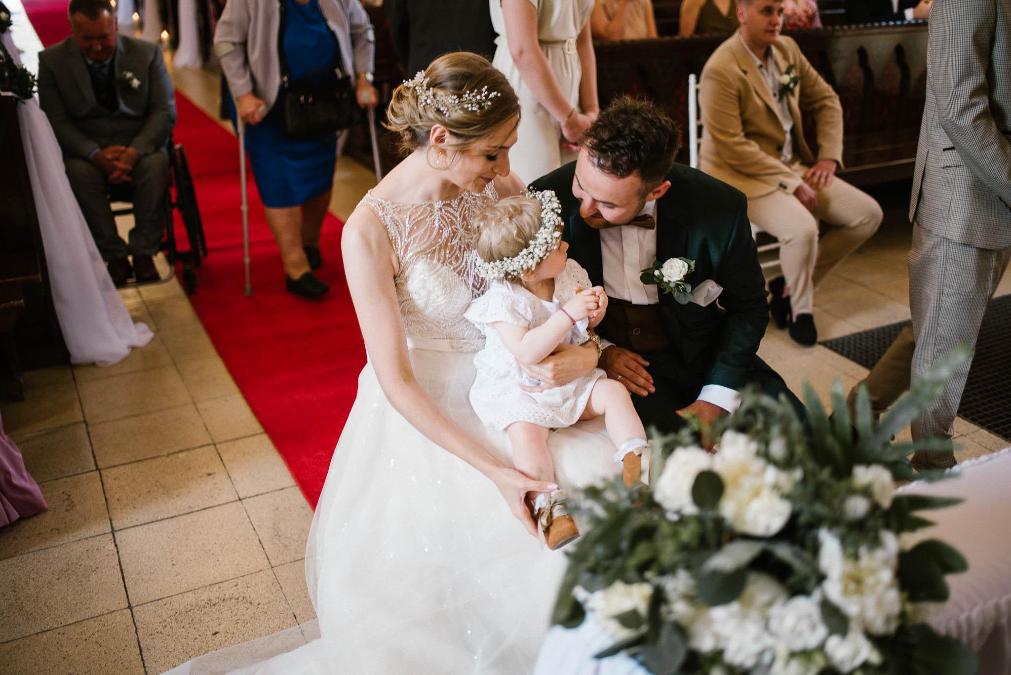 Córeczka z rodzicami siedzą przed ołtarzem -  ślub w Stodole Bojanowo