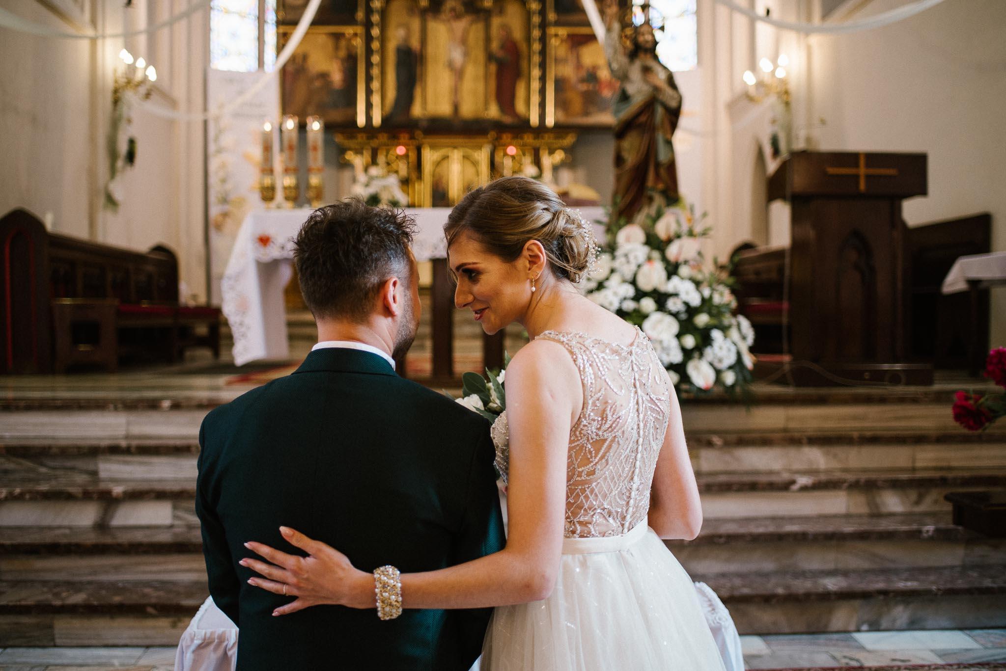 Żona szepcze na ucho do męża -  ślub w Stodole Bojanowo