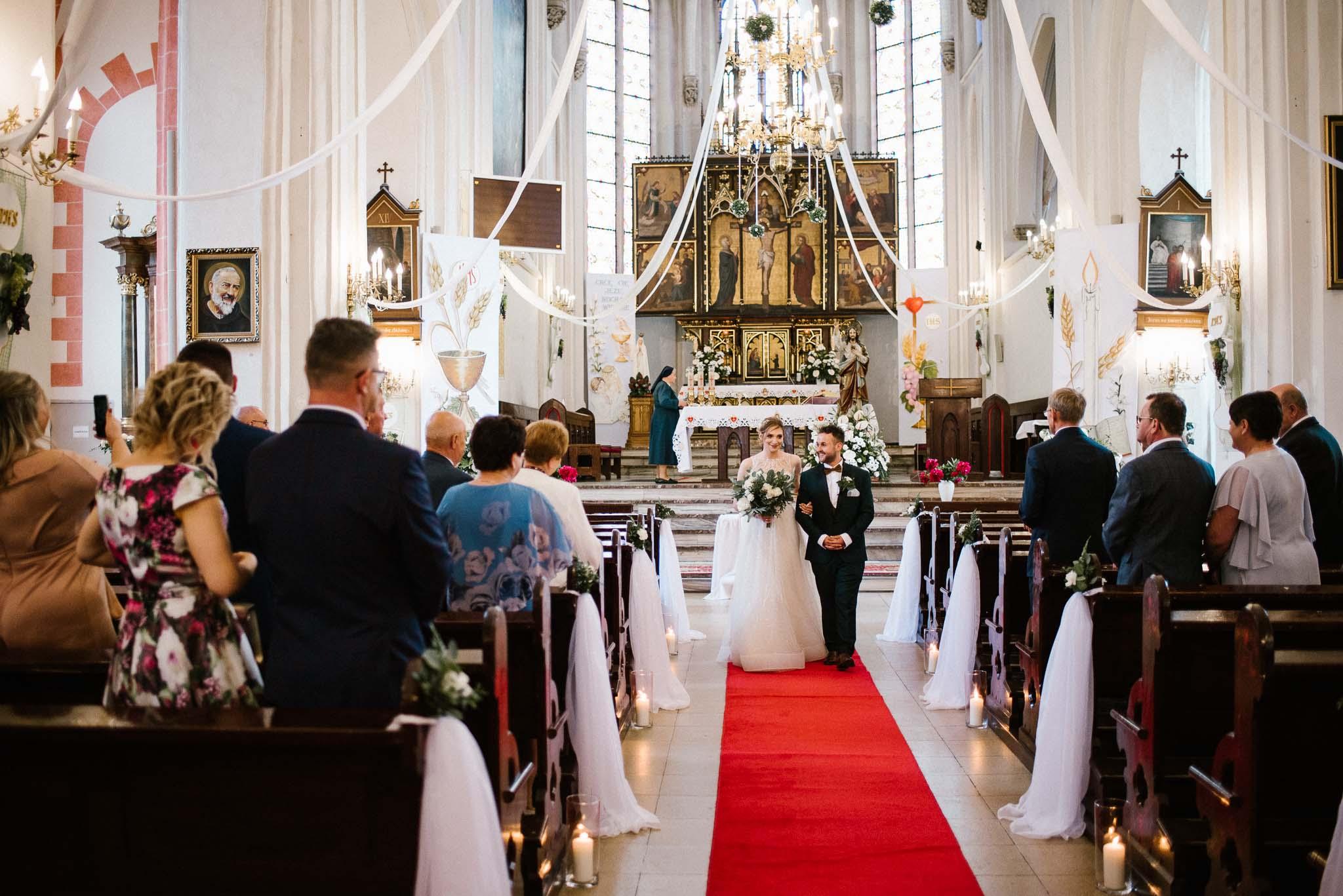 Para młoda wychodzi z kościoła -  ślub w Stodole Bojanowo