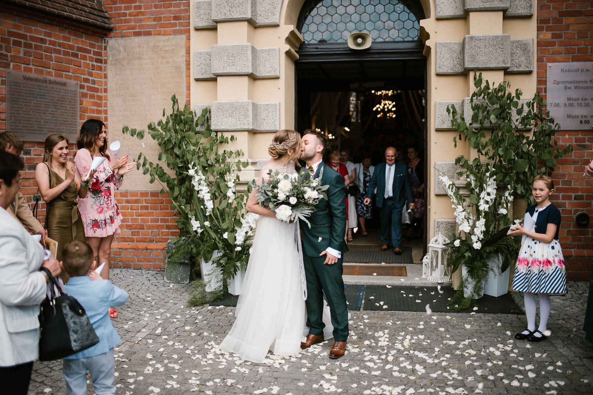 Państwo młodzi przed kościołem się całują -  ślub w Stodole Bojanowo