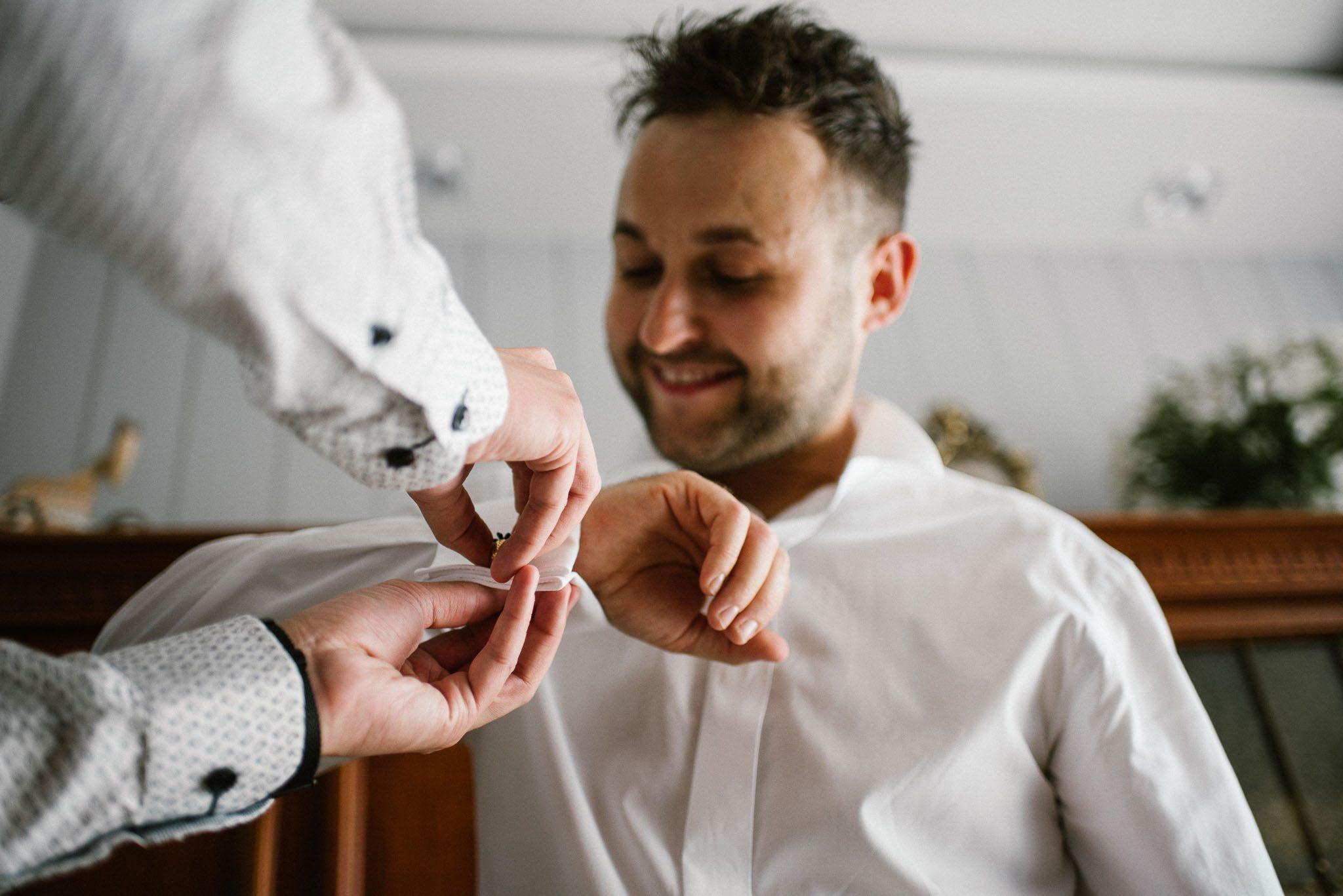 Świadek pomaga panu młodemu zapiąć spinki do koszuli - ślub w Stodole Bojanowo