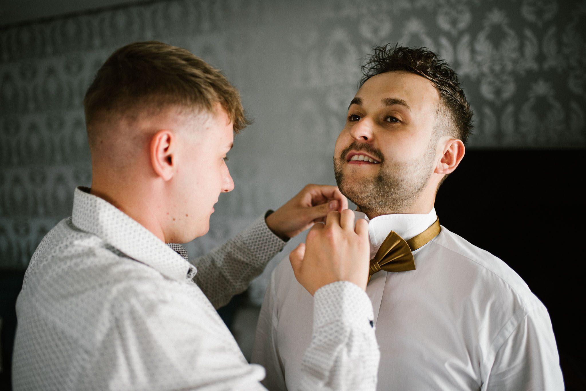 Świadek pomaga panu młodemu założyć muchę - ślub w Stodole Bojanowo