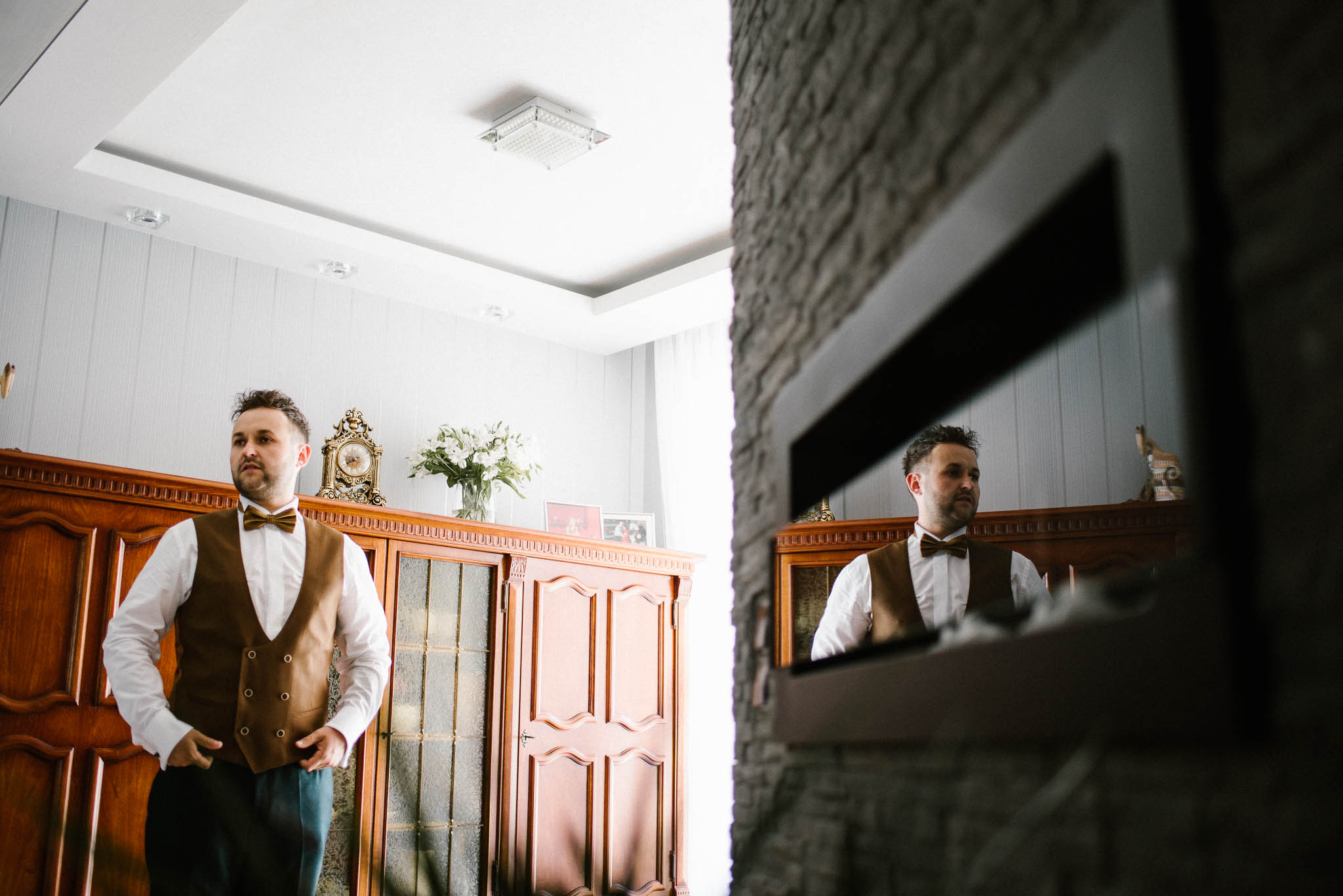 Pan młody ma założoną brązową kamizelkę - ślub w Stodole Bojanowo