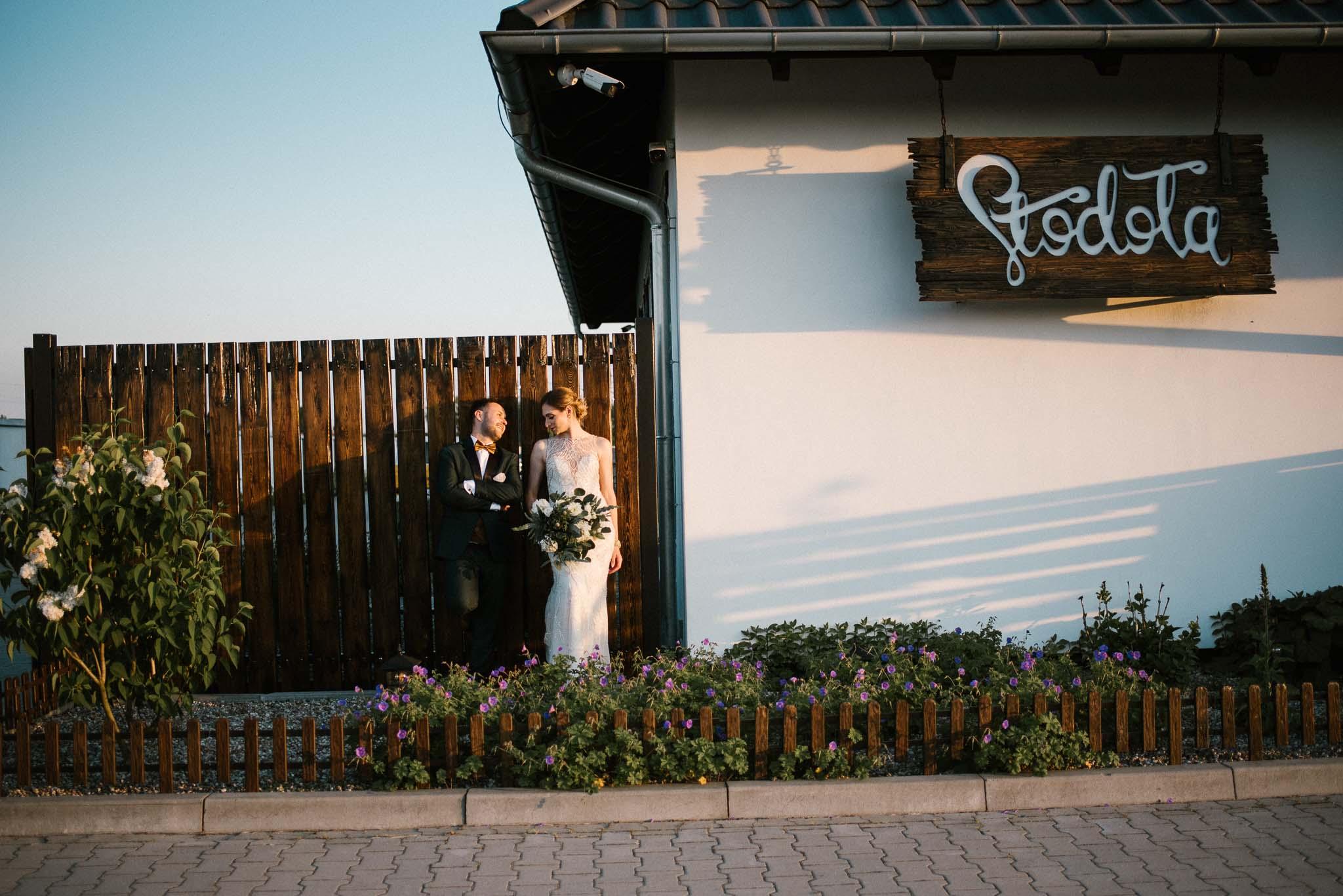 Para młoda pozuje przy drewnianym płocie -sesja ślubna w plenerze Stodoła Bojanowo
