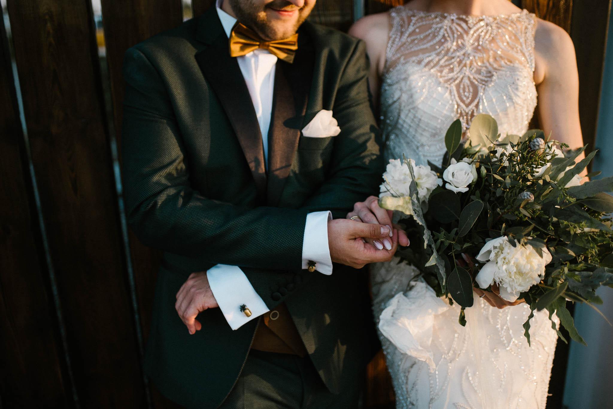 Para młoda trzyma się za ręce - sesja ślubna w plenerze Stodoła Bojanowo