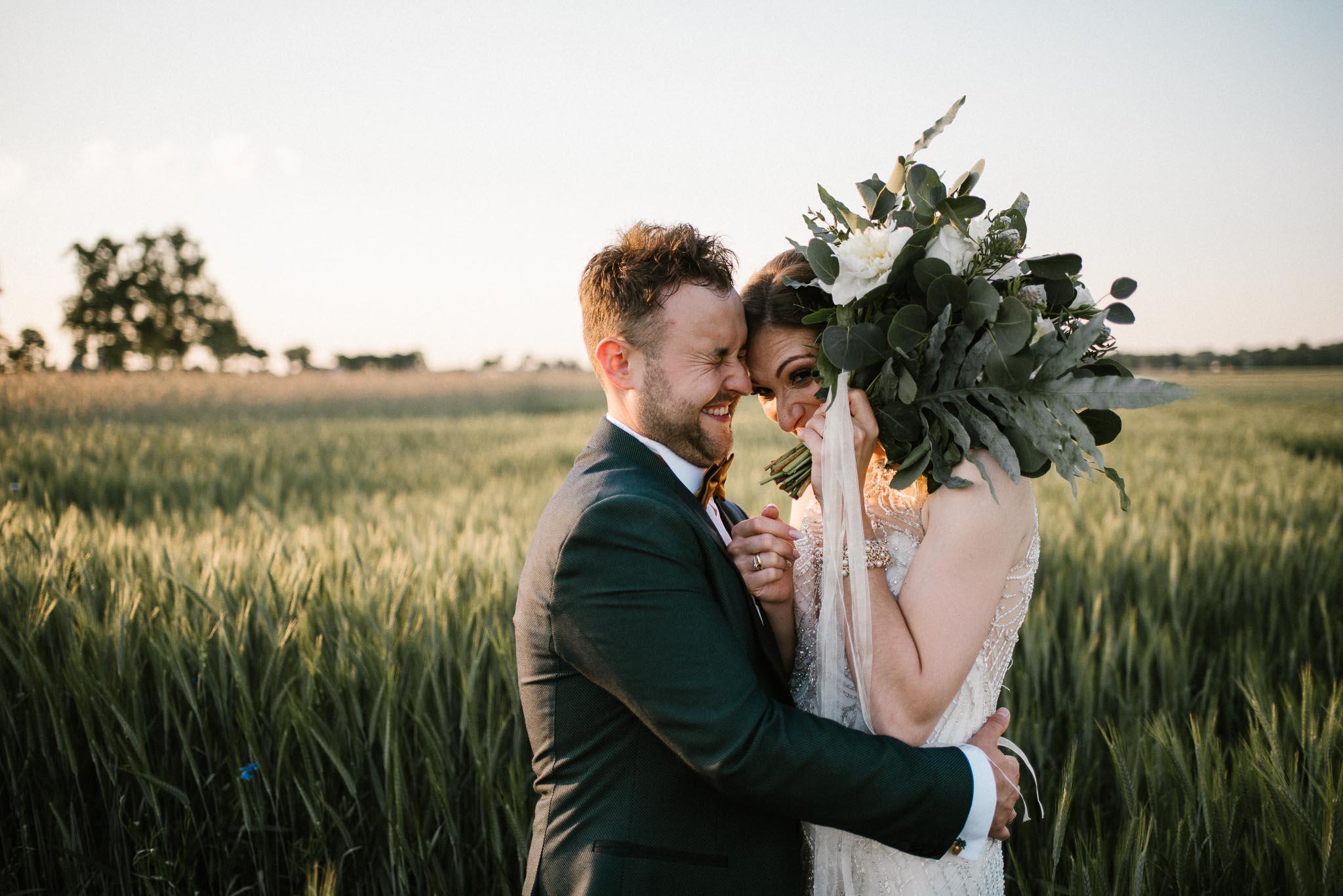 Panna młoda zasłania się bukietem ślubnym - sesja ślubna w plenerze Stodoła Bojanowo