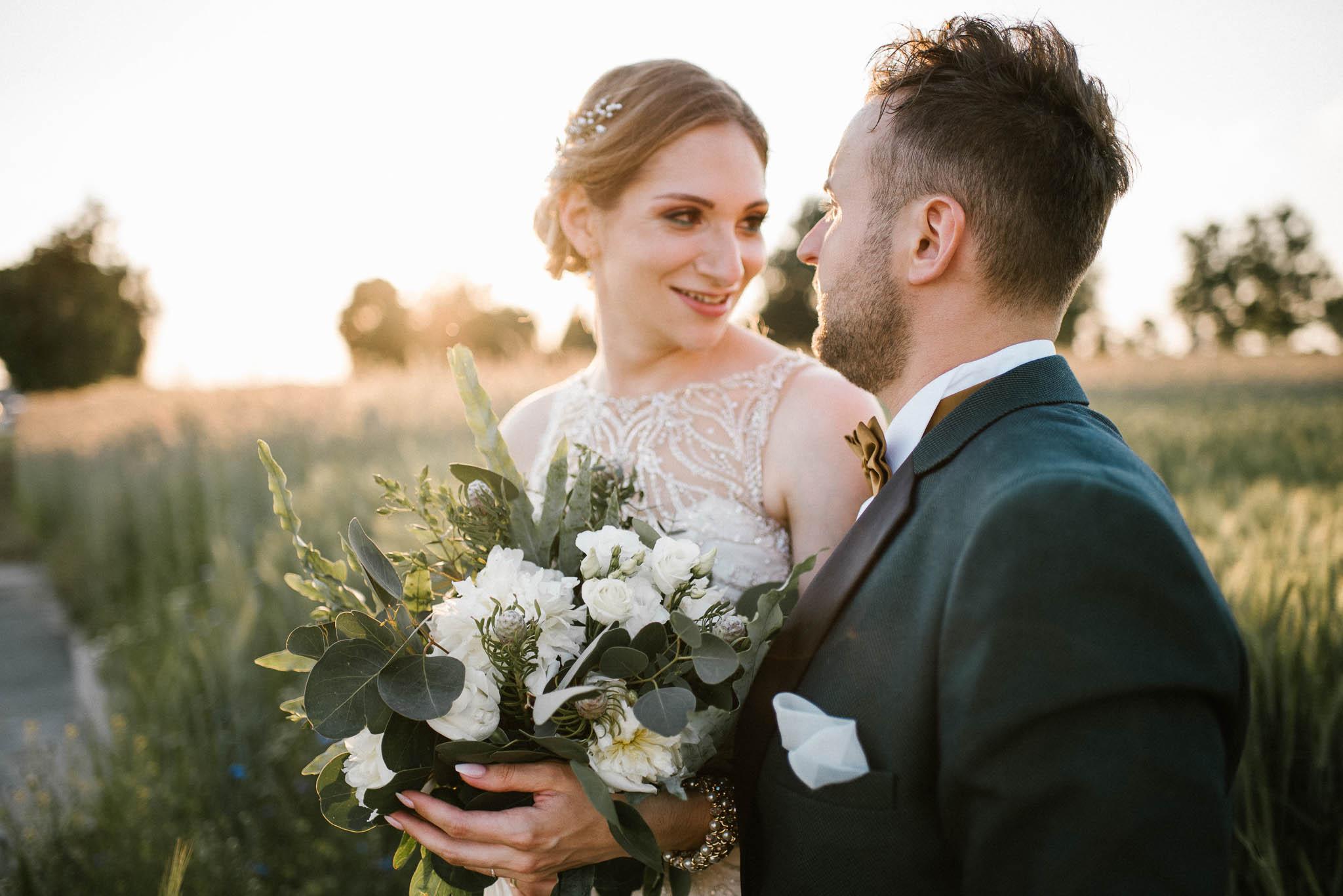 Para młoda patrzy sobie w oczy - sesja ślubna w plenerze Stodoła Bojanowo