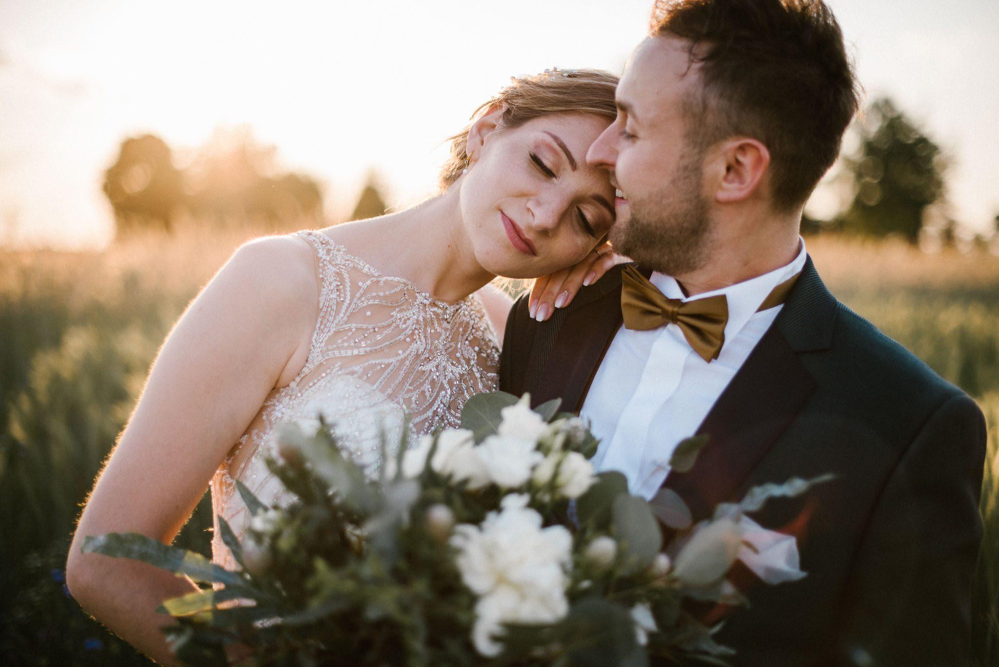 Panna młoda przytula się do pana młodego - sesja ślubna w plenerze Stodoła Bojanowo