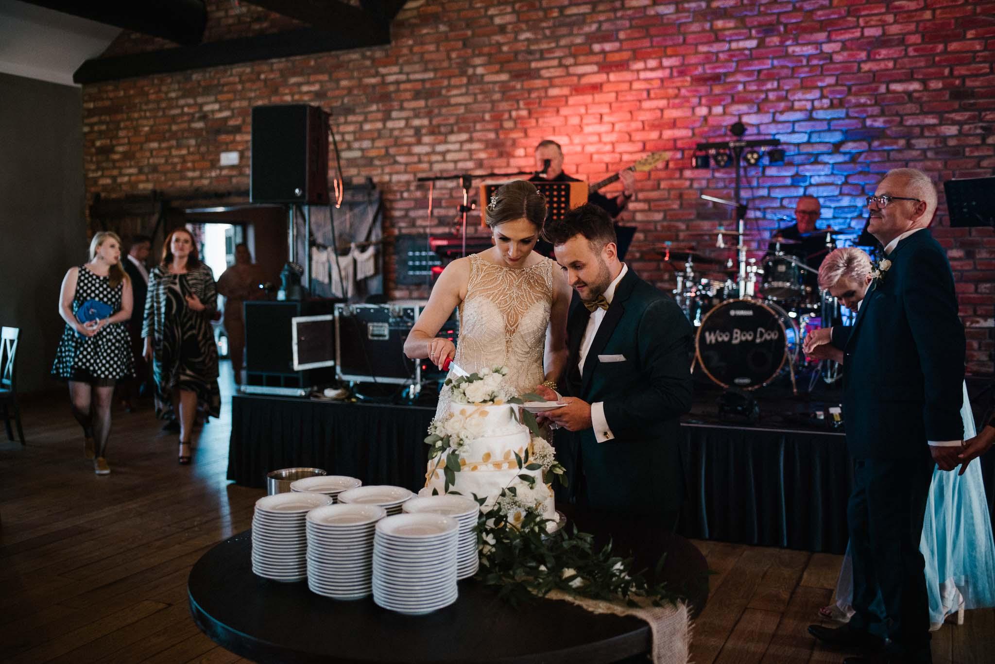 Para młoda kroi tort na weselu -ślub w Stodole Bojanowo