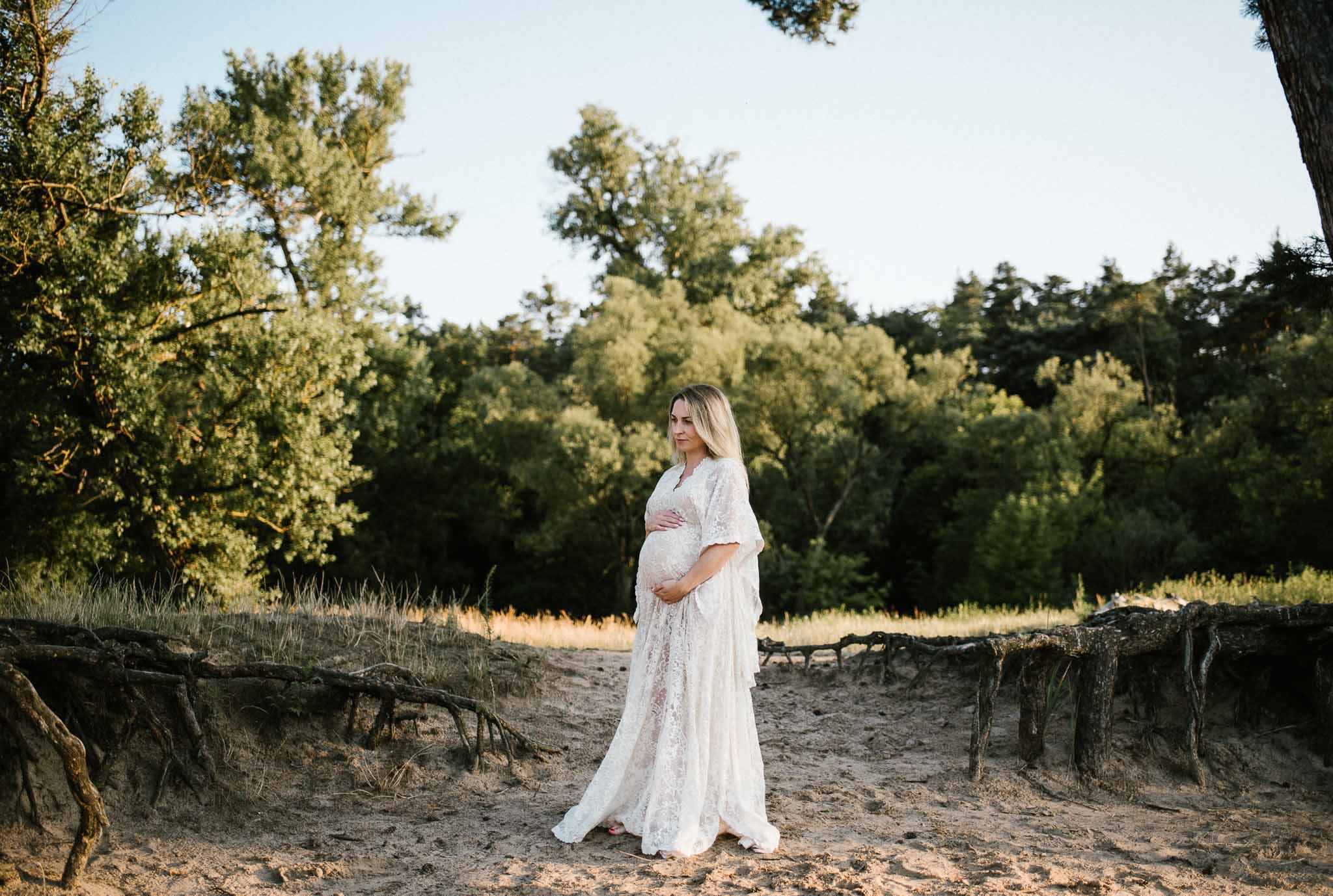 Kobieta w ciąży stoi w wąwozie w sukni koronkowej boho Sesja ciążowa w plenerze w wodzie Poznań