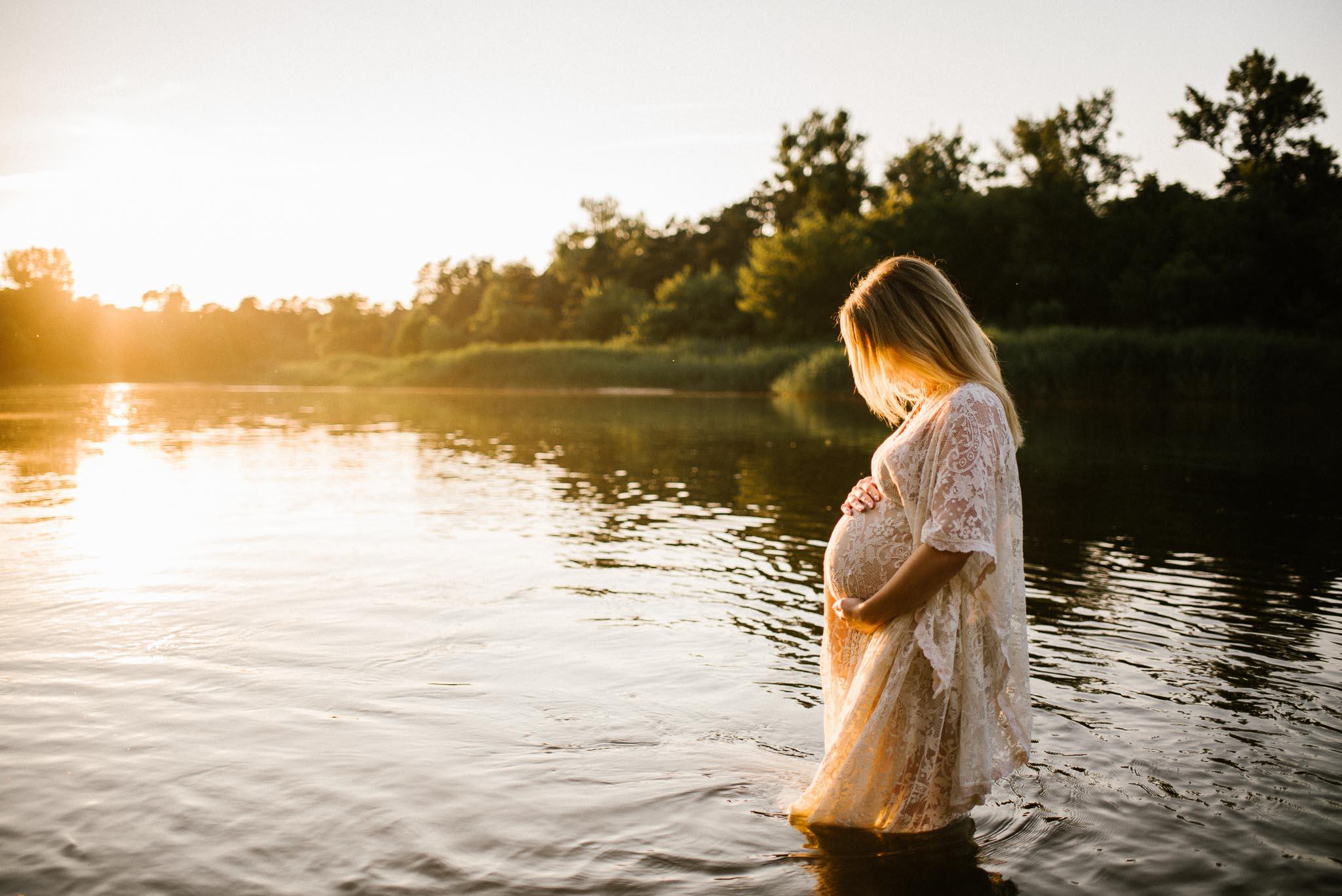 Kobieta wchodzi do jeziora i obejmuje ciążowy brzuch - Sesja ciążowa w plenerze w wodzie Poznań
