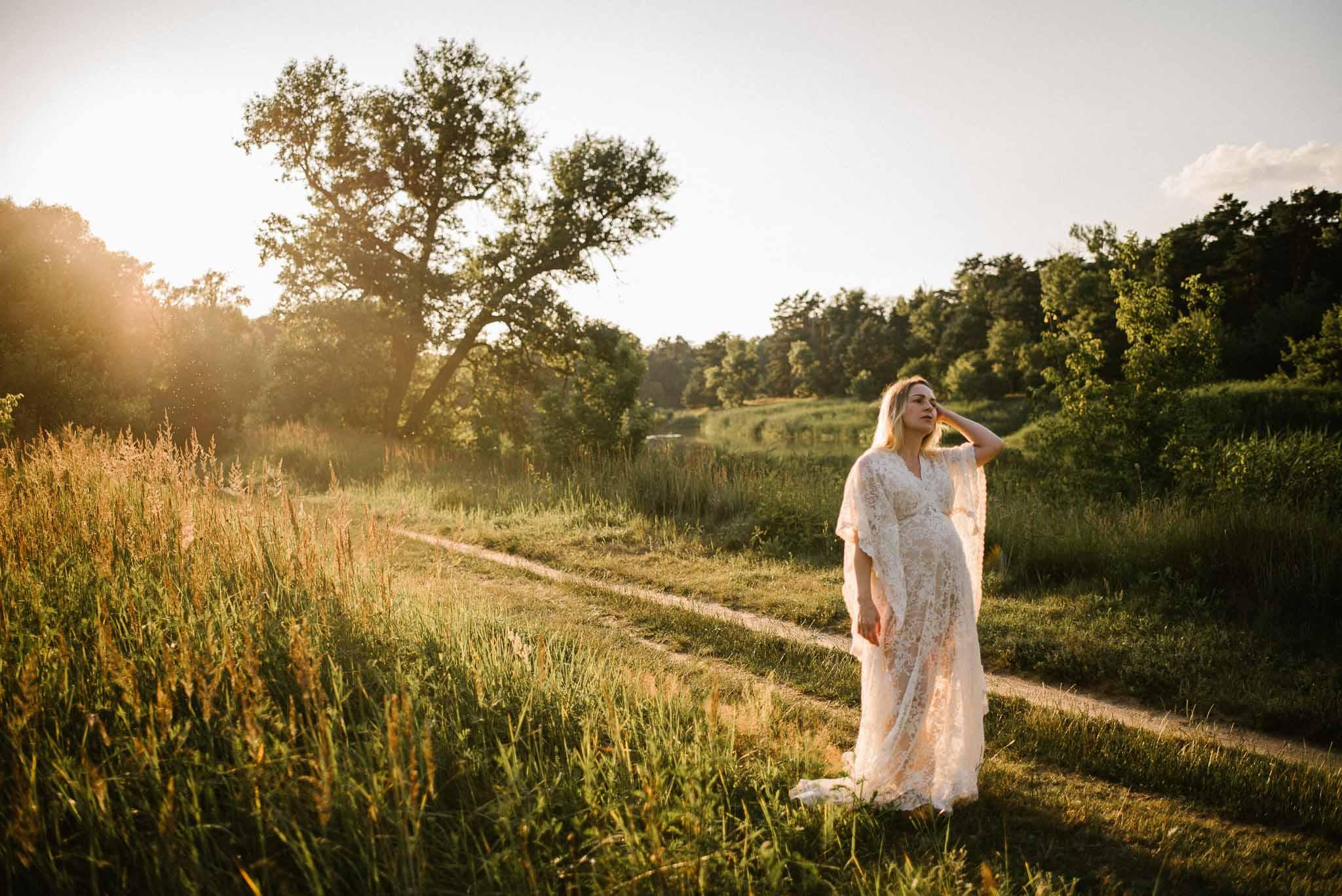 Kobieta w boho koronkowej białej sukni w ciąży idzie ścieżką  - Sesja ciążowa w plenerze w wodzie Poznań